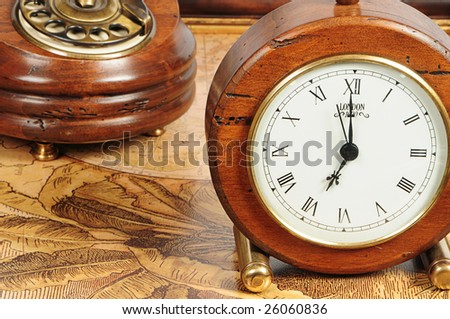 old-fashion objects as background: wooden clock and telephone - stock photo