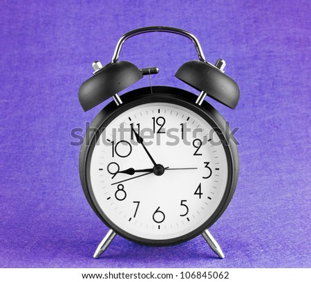 Old-fashioned alarm clock isolated on a purple background