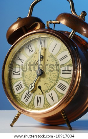 Old fashioned alarm clock on a blue background. - stock photo