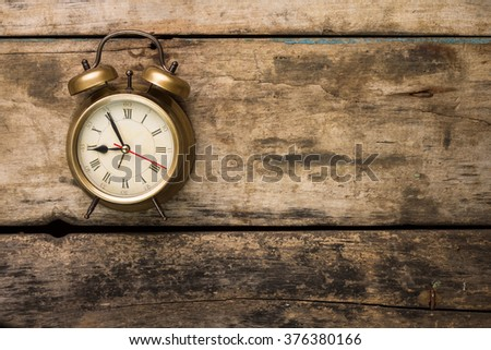 Old fashioned alarm clock on wooden background. Deadline or start time top view  background with copy space - stock photo
