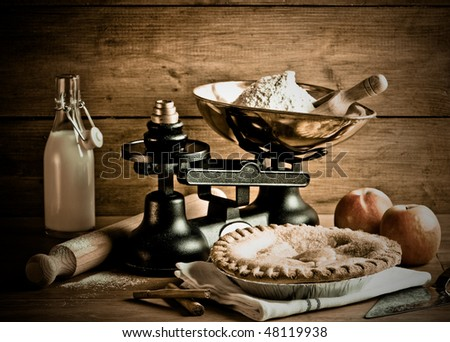 Old fashioned apple pie dessert with antique weighing scales - stock photo