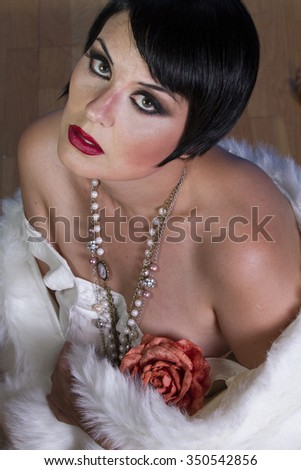 Old-fashioned beautiful brunette girl 20s style flapper with jewels and white fur - stock photo