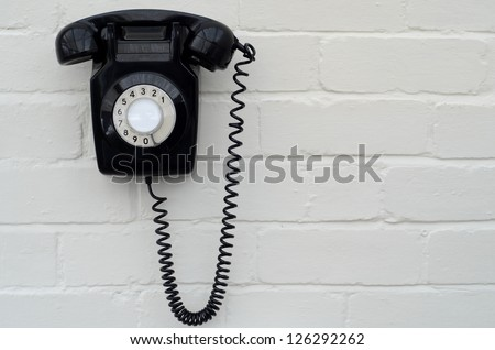 Old fashioned black Bakelite telephone on a painted brick wall - stock photo