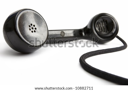 Old-fashioned black telephone receiver with cord on white background - stock photo