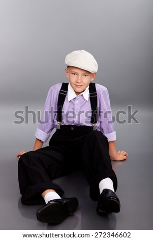 Old fashioned boy sitting and looking to the camera on gray background - stock photo