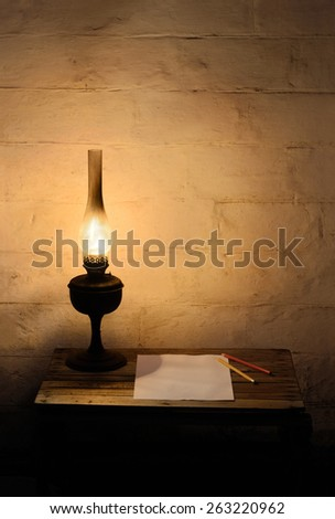 Old fashioned burning kerosene lantern, a blank sheet of paper and two pencils on old wooden table near old brick wall in the darkness - stock photo