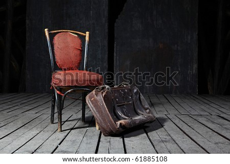 Old fashioned chair and well-traveled vintage suitcase on wooden floor