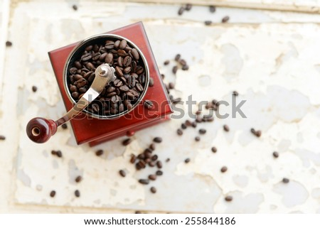Old-fashioned coffee grinder with coffee beans - stock photo
