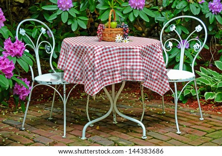 old-fashioned ice cream table and chair in a rhododendron garden - stock photo
