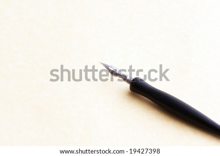 old fashioned ink dip pen for writing or drawing on parchment paper background