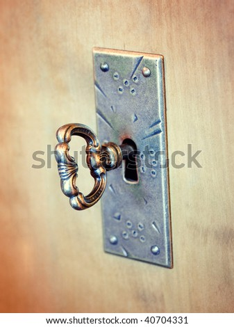 Old-fashioned key in a keyhole - stock photo