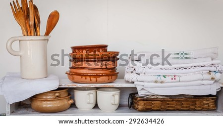 Old fashioned kitchen style concept. Concept include folded rustic linen embroidery, folded kitchen old clay plates with pottery of wooden utensils over on shelves.  - stock photo