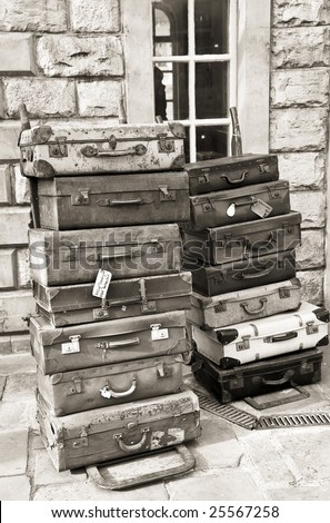 old fashioned luggage cases stacked high - stock photo