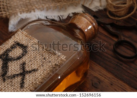 Old fashioned medicine bottle (with handwritten letters on burlap tag), antique scissors, and fabric bandages on rustic wood background.  Low key still life with directional, natural lighting. - stock photo