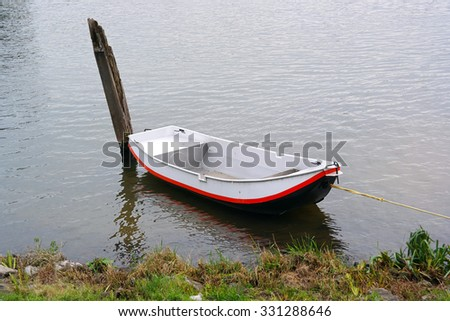 Old-fashioned moored iron row boat on Maas river in The Netherlands - stock photo