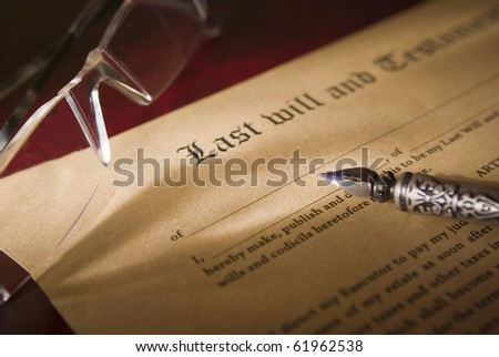 Old-fashioned paper with text of Last will and focus on antique quill