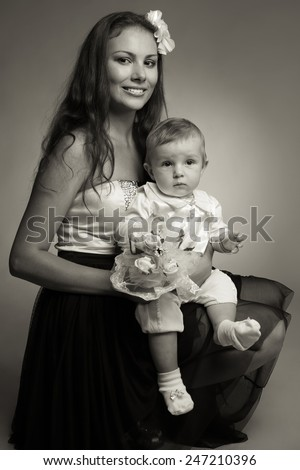 Old fashioned portrait concept. Beautiful mother hugging her gorgeous baby boy in trendy vintage clothing over gray background. Family posing & looking at camera. Retro hipster style. Studio shot - stock photo