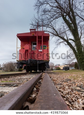 Old fashioned RR Railroad red caboose with rail leading to it in Warrenton, VA