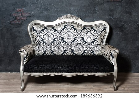 Old-fashioned sofa against the background of black wall - stock photo