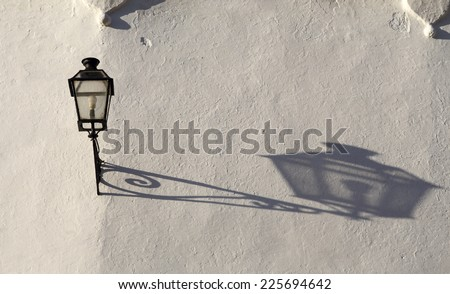 Old fashioned street light throwing a long shadow on a white-washed wall in the late afternoon sunshine. Seville, Andalusia, Spain. - stock photo
