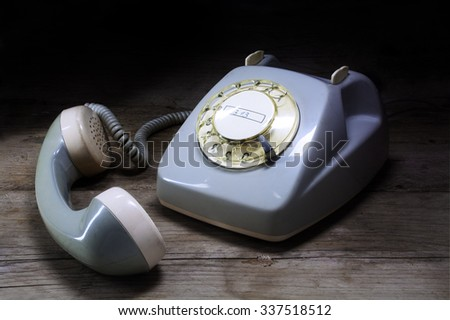 old-fashioned telephone of gray plastic with rotary dial and removed receiver on a dark wooden table - stock photo
