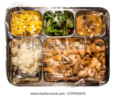Old fashioned Thanksgiving TV dinner on metal tray covered in plastic - stock photo