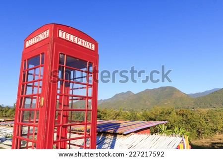 Old-fashioned traditional red telephone booth or public payphone standing Amidst the mountainous backdrop - stock photo