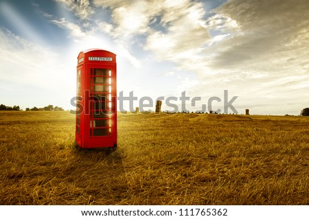 Old-fashioned traditional red telephone booth or public payphone standing in an open deserted field in evening light - stock photo