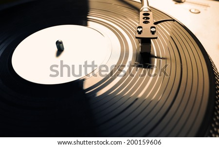 Old fashioned turntable playing a track from black vinyl in golden light. - stock photo