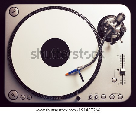 Old fashioned turntable playing a track from white vinyl. Shot from above, vintage cross processing. - stock photo