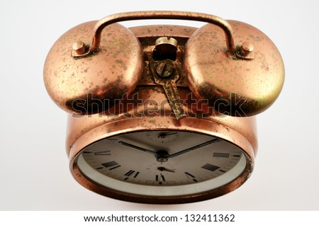 old-fashioned vintage copper alarm clock  over white - stock photo