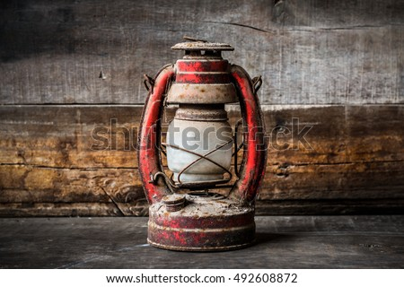 Old fashioned vintage kerosene oil lantern lamp burning with a soft glow light with aged wooden floor with copy space