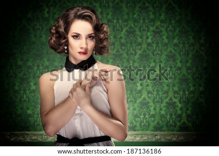 Old-fashioned woman vintage toning on retro green background. Professional make up and hairstyle. Studio lighting - stock photo