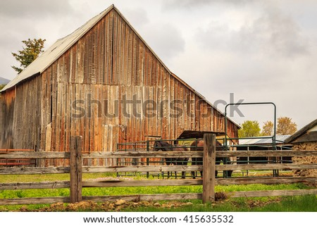 Old fashioned wooden barn and horses in rural Utah, USA. - stock photo