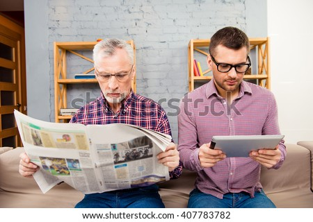 Old father reading newspaper and his son using tablet - stock photo