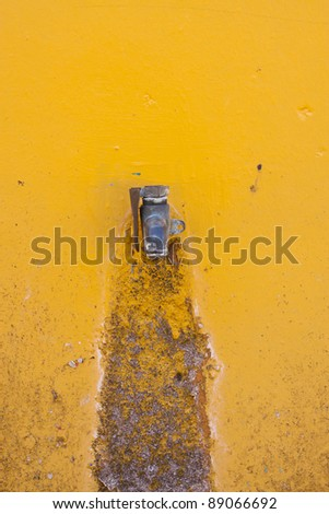 old faucet on yellow wall background - stock photo