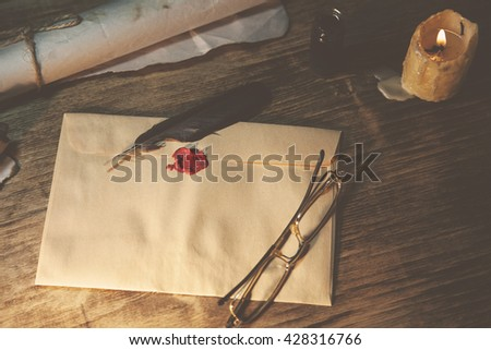 Old feather, envelope and  sealing wax on wooden table - stock photo