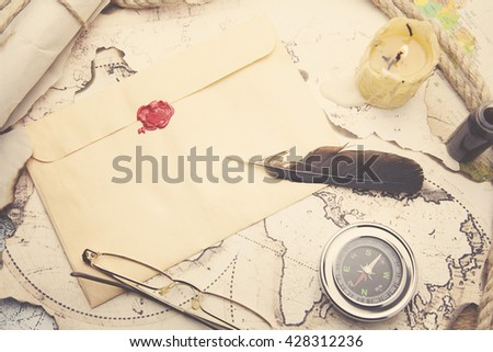 Old feather, envelope, sealing wax on the map - stock photo