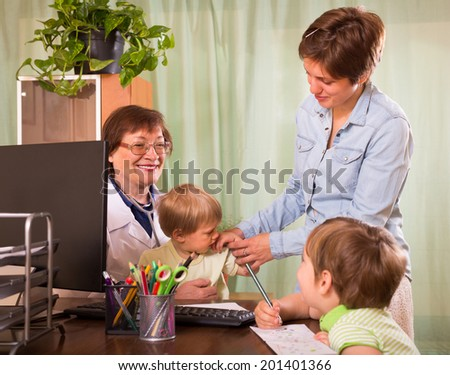 Old female pediatrician doctor examining children in clinic - stock photo