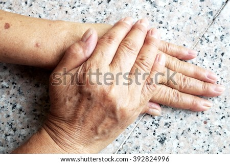 Old female/woman hands on marble background. - stock photo