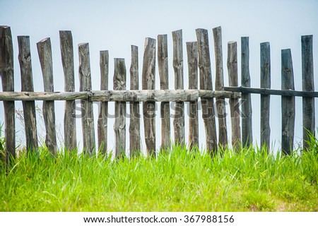 Old fence on the green lawn in garden with blue sky as a background