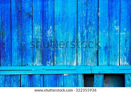 Old fence planks painted in bright blue color - stock photo