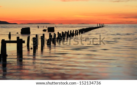 Old fence posts leading into the Great Salt Lake, Utah, USA. - stock photo
