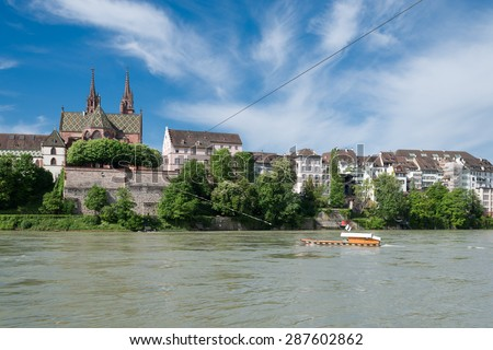 Old ferry crossing the Rhine river at Basel, Switzerland. In the background the famous Basel cathedral, one of the top spots for tourists. - stock photo