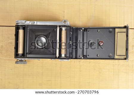 Old film camera on wooden background open - stock photo