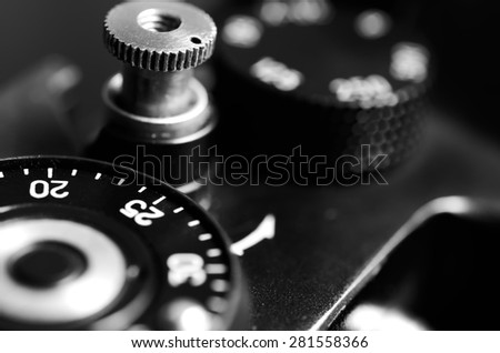 Old film DSLR camera. The wheel of choice shutter and shutter button. Close up view. Macro. Selective focus. Vintage photo. Black and white. - stock photo