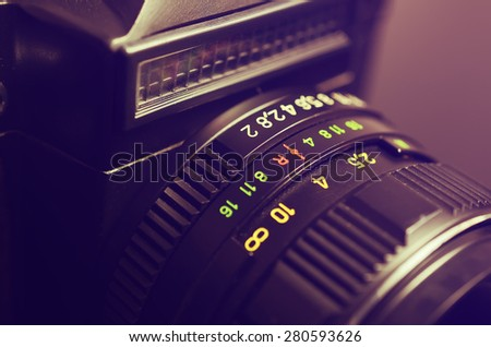 Old film DSLR camera with lens. The scale of the aperture, depth of field and distance. Close up view. Macro. Selective focus. Vintage photo. Toning. - stock photo