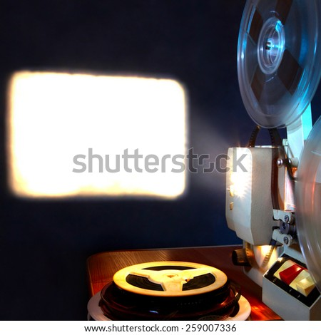 Old film projector show the film in dusk onto a wall - stock photo