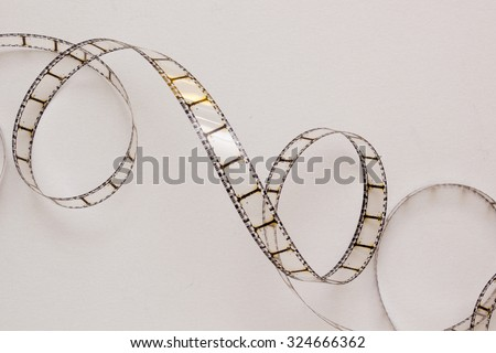 Old film strip, rolled on a white background. - stock photo