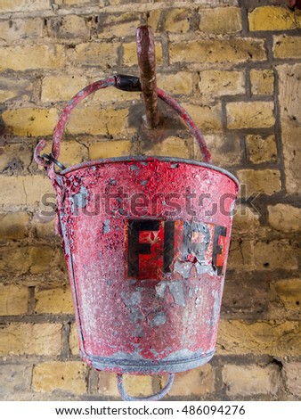 Old fire bucket hanging on a brick wall